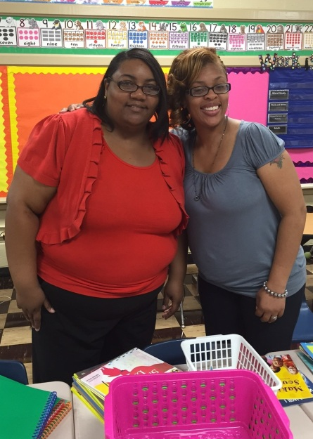 DeMia Mays (R) assisting a teacher with classroom setup.