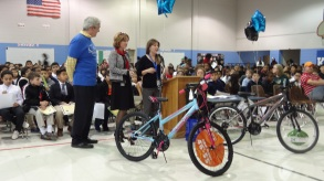Branch Manager George Bravos (L) and VP of Retail Tara Smith (C) present bikes donated by Orion to students who achieved perfect attendance during the fall semester.