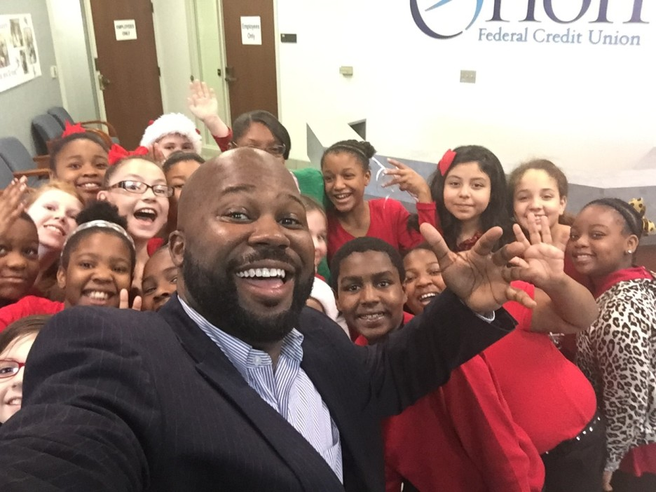 Director of Retail Ron Brooks takes a selfie with the KBE Choir in the Kate Bond Branch lobby. The choir visited in December to treat us with a medley of holiday songs.