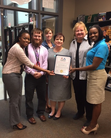 Assistant Branch Manager Takeshia Smith (L), and Business Development Officer Trevia Chatman (R) receiving a Certificate of Appreciation from WSM's principal & staff.
