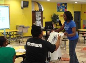 Orion BDO, Trevia Chatman (right) distributes tees to Havenview's teachers