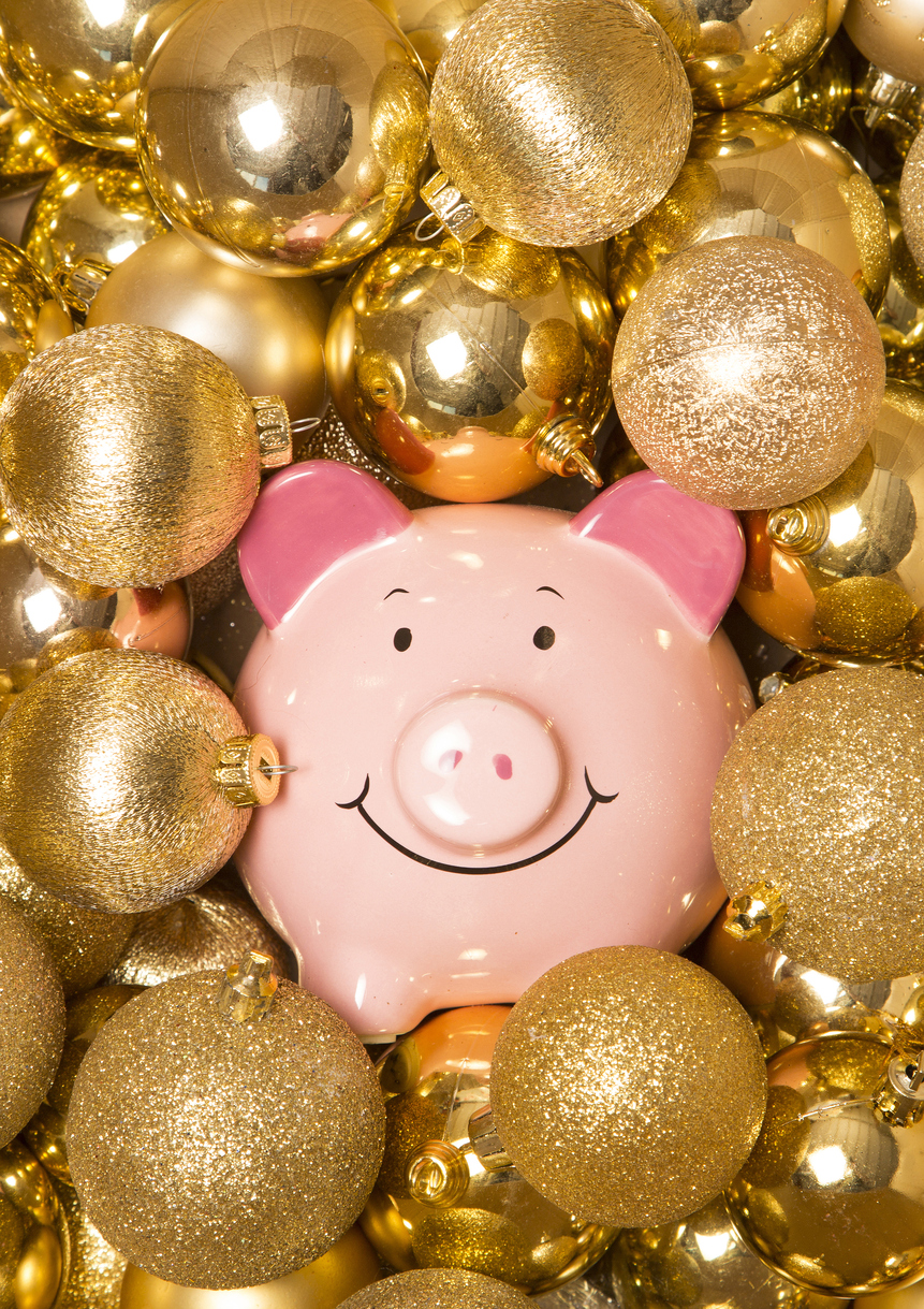 Saving money at christmas piggybank on gold baubles